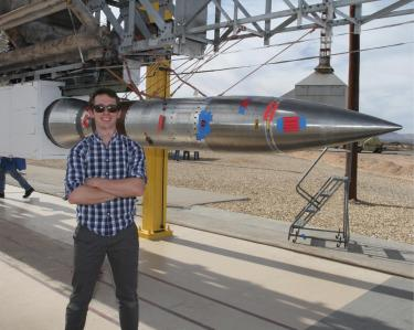 Nick Erickson in front of a rocket