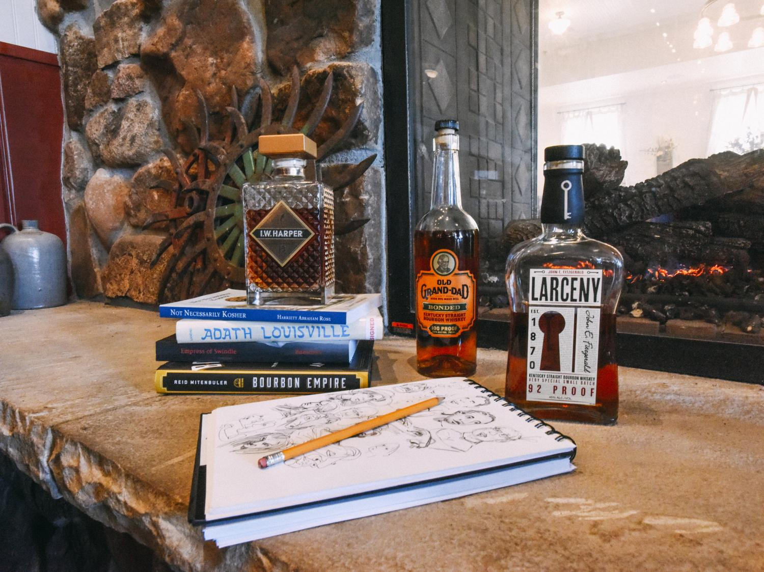 JT Waldman's sketch book surrounded by bottles of bourbon