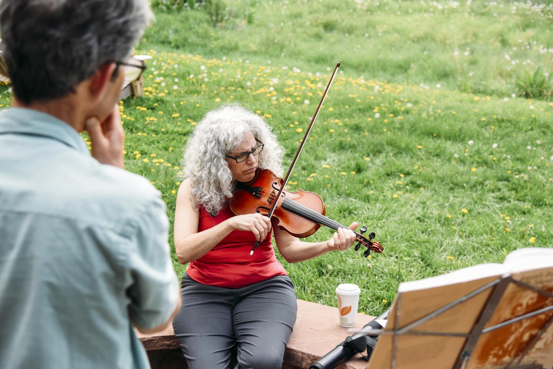 Alicia Svigals playing violin and Yonatan Malin watching her