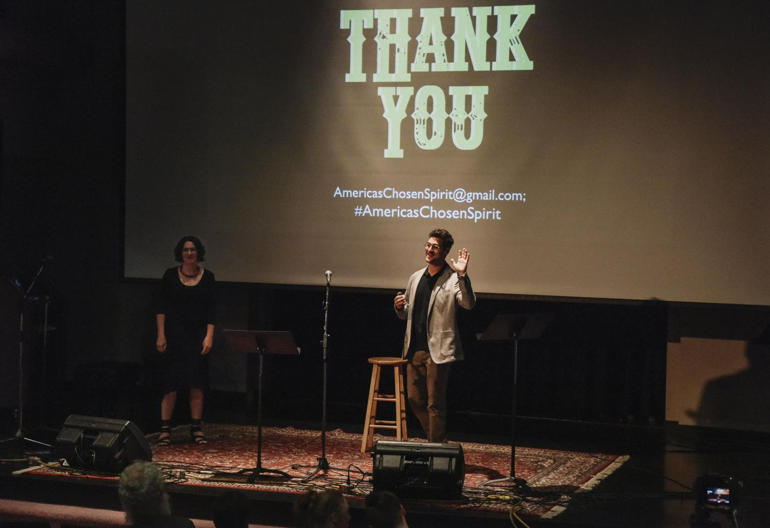 "Janice Fernheimer and JT Waldman standing on stage, a ""thank you"" on the screen behind them"