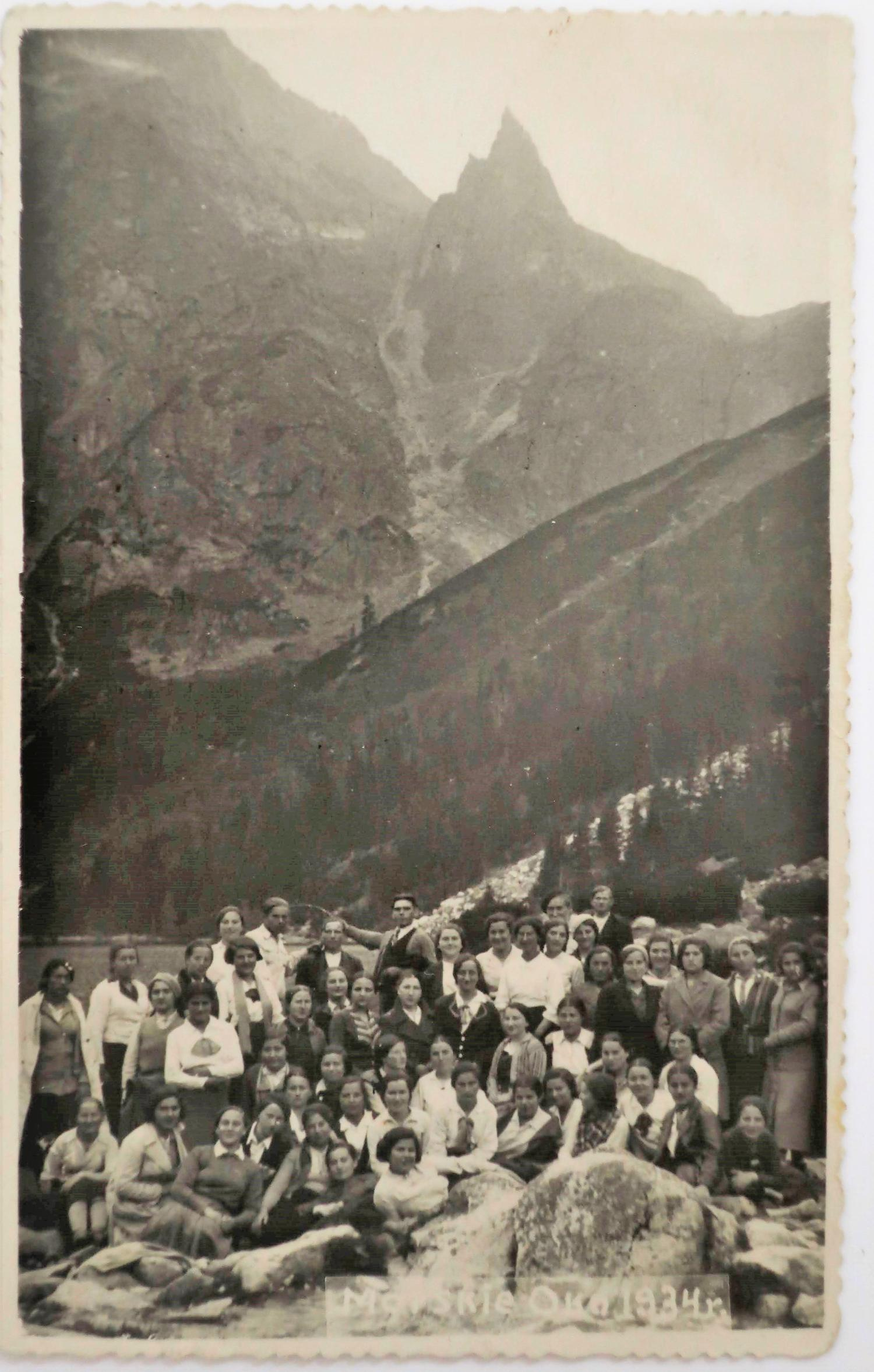 a group of people standing by mountains.