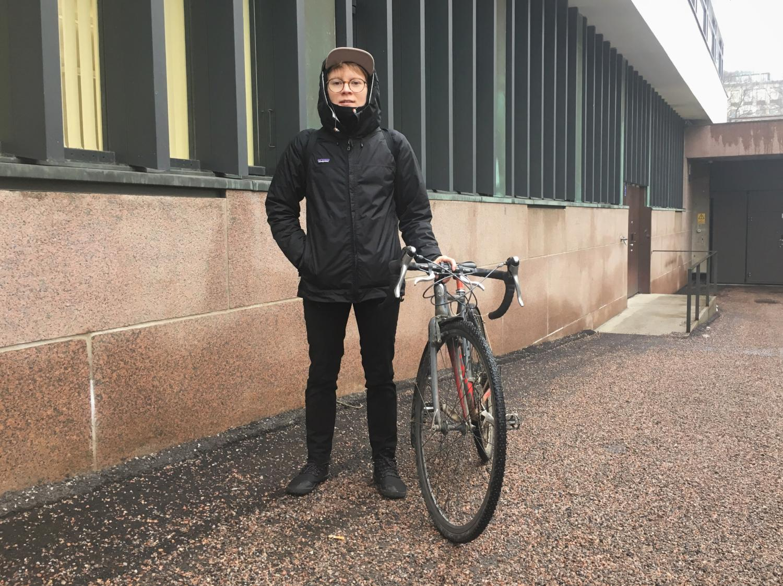 Emil Uuttu standing besides her bike