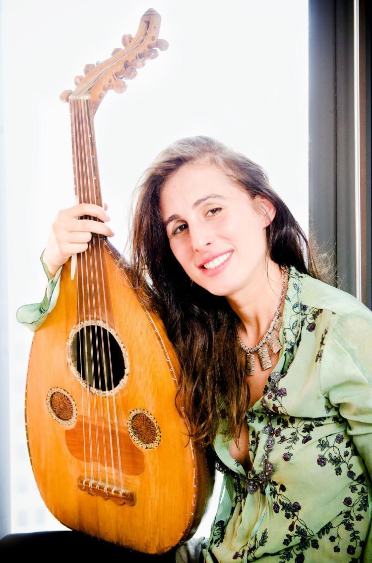 Basya Schechter sitting and holding an instrument.