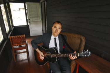 Jeremiah Lockwood playing guitar on Chautauqua porch