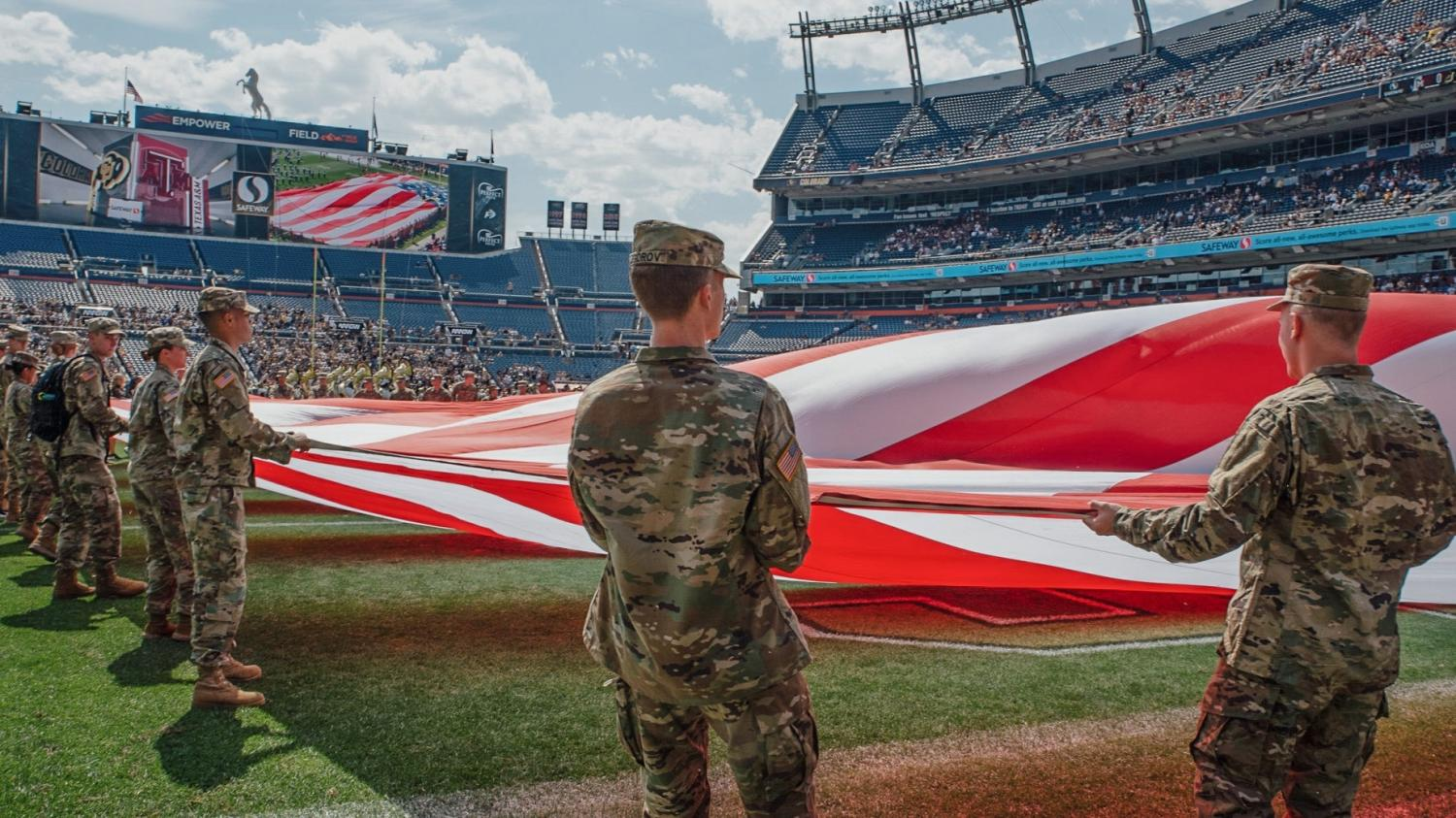 AROTC Cadets holding a large U.S. Flag on the field at Mile High for the 9/11 remembrance event. Photo courtesy of Cadet Decker.