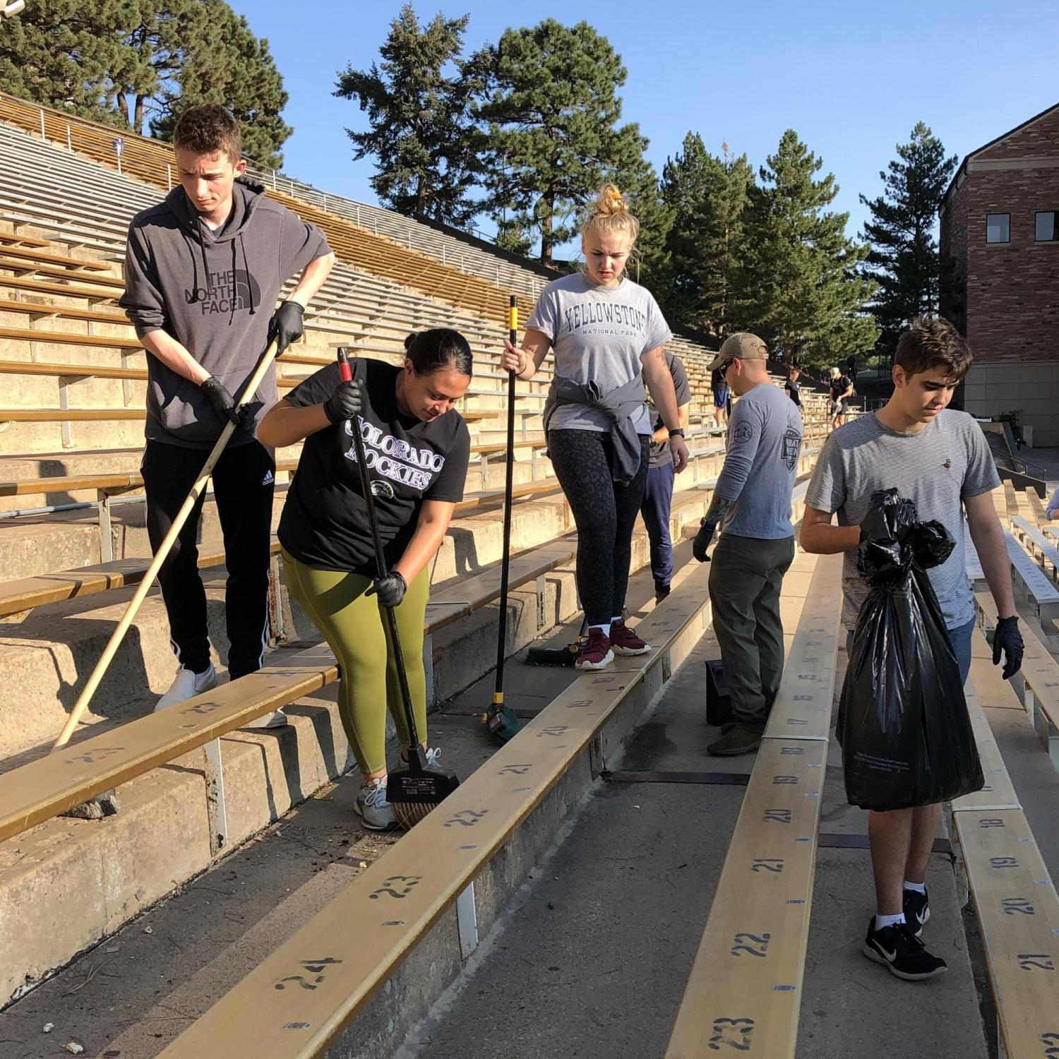 Army ROTC Cadets use brooms behind the leaf-blowers to make the final sweep of the stadium.