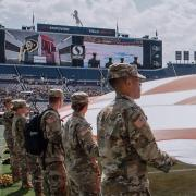 Army ROTC Cadets holding the U.S. flag and watching themselves on the big jumbotron screen. Photo courtesy of Cadet Arianna Decker.