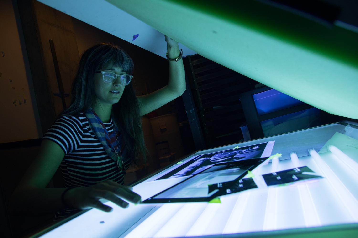 Student reviewing negatives at the light box in the darkroom studio