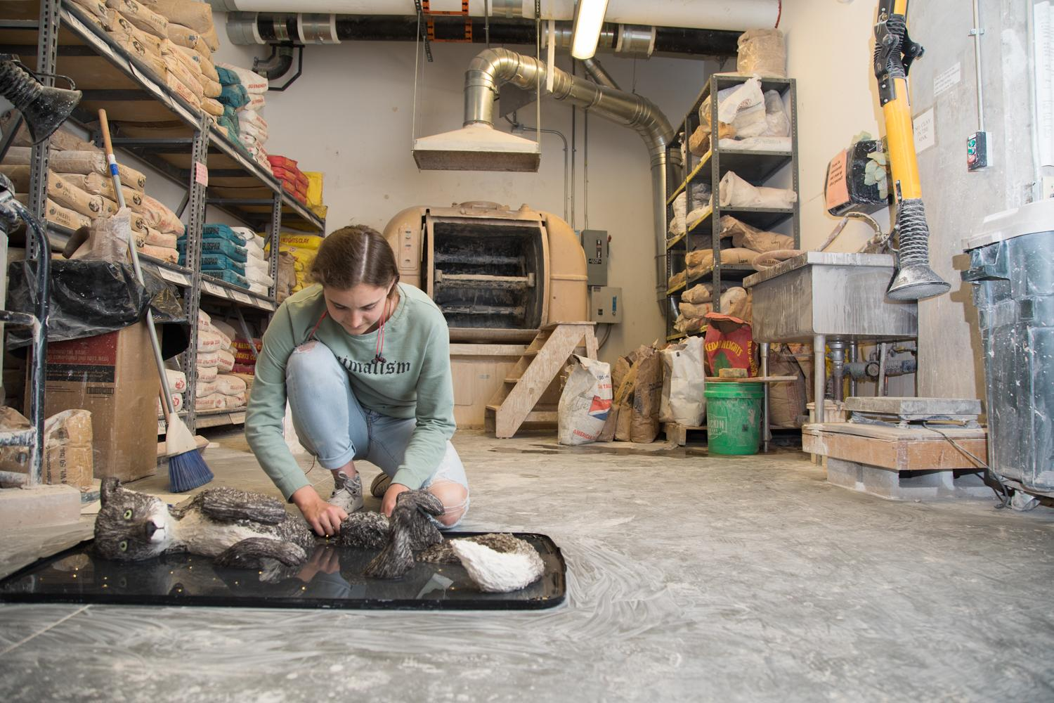 Student working on clay piece in the kiln room
