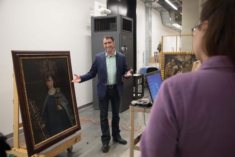 James Cordova examining painting in the Art Museum
