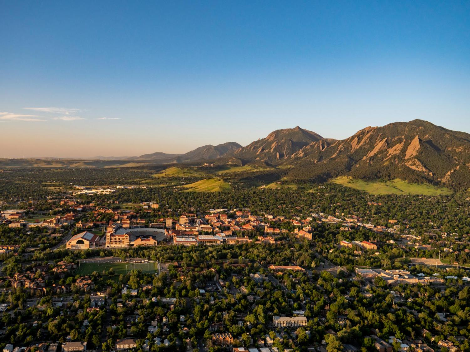 Ariel view of CU Boulder campus with flat iron mountains in background
