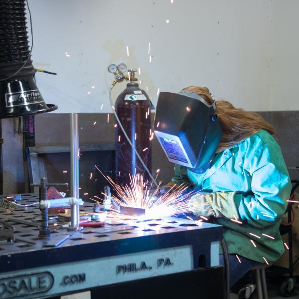 student working on metal artwork using welder