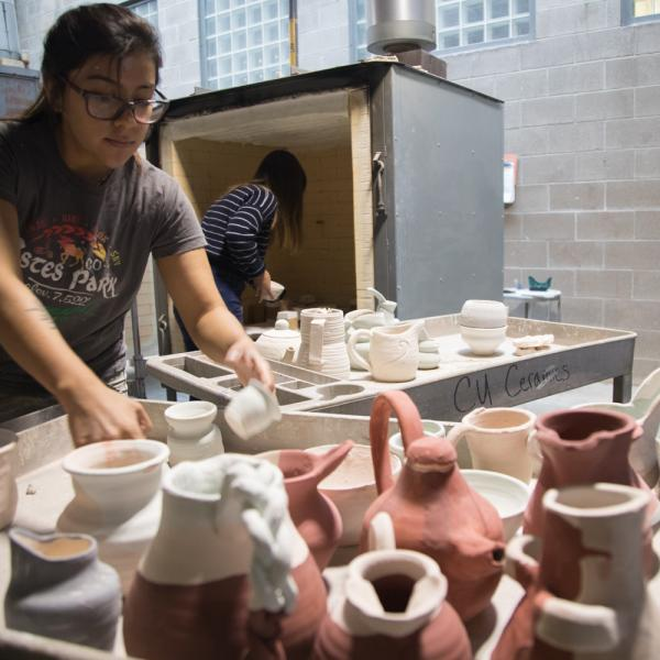 Student with clay sculptures loading into the kiln