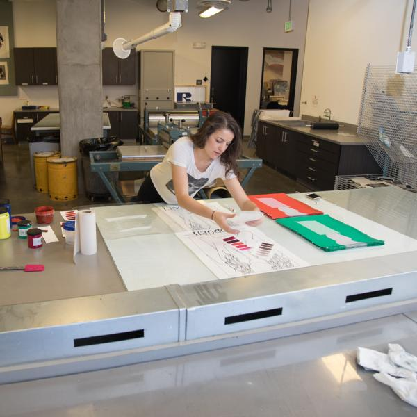 A printmaking student prepares materials and ink in the classroom for a project.