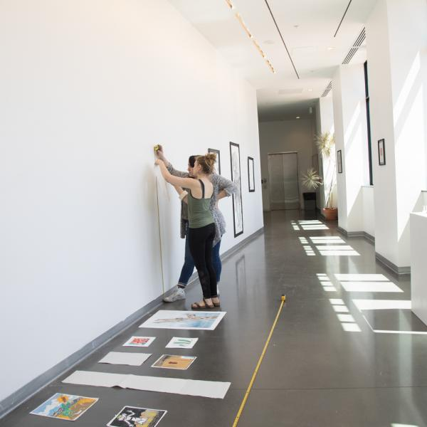 Students hanging artwork in the exhibition space on the third floor