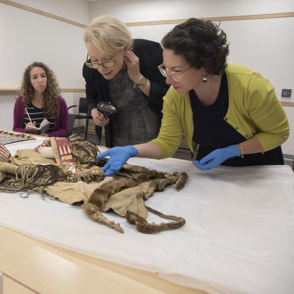 Annette de Stecher and Hope Saska studying Native American object in CU Art Museum
