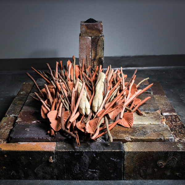 """Joelle Cicak. """"Will your legs carry you to the safety of Spring? Or will they be removed at the knees and disposed of, like Autumn's sticks and leaves?,"""" Stoneware, Earthenware, Hard brick, Ash from a whitetail deer's forelegs (gift from a hunter who had no use for them). 34""""x29""""x18"""". 2018"""