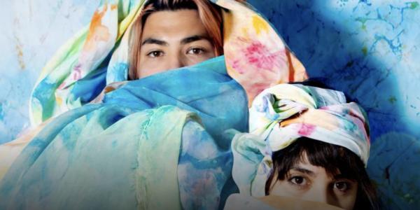 Alejandra Abad and Román Anaya, collaboratively known as Abad◮Anaya, pose draped in hand-colored fabrics. (Credit: Alejandra Abad and Román Anaya)