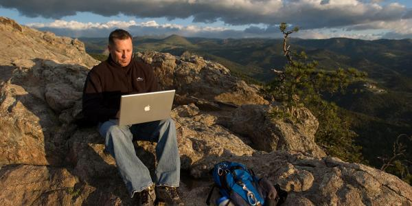 student with computer in scenic Boulder Colorado mountains