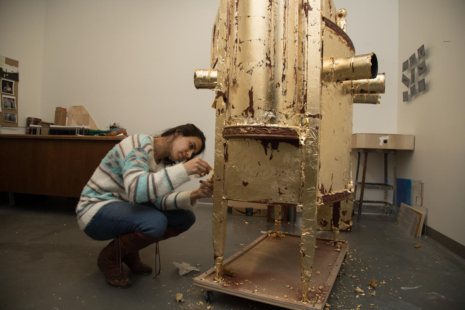 MFA candidate and IMAP graduate student, Yasmin Mazloom, applies gold leaf to her MFA thesis project in her studio.