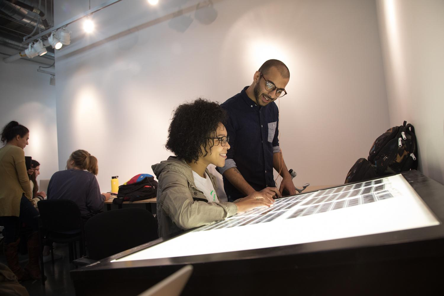 Two students looking at negatives on a lightbox