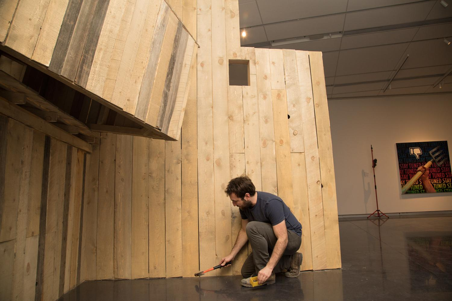 MFA candidate and graduate student, Aaron Treher, works on his large scale wood installation and makes some adjustments in preparation for the master of fine arts thesis exhibition in the gallery of the art museum.
