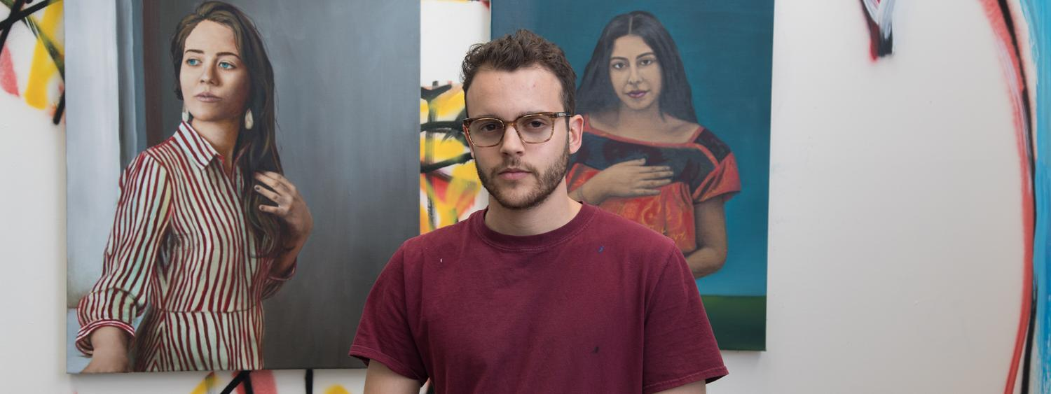 Drawing & painting student and BFA candidate, Gabriel Sanchez, posing in front of his paintings in his studio.