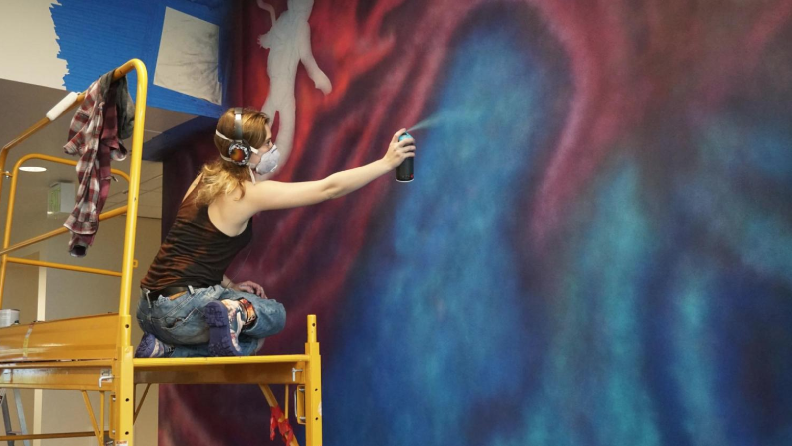 Ellie Marcotte painting a mural
