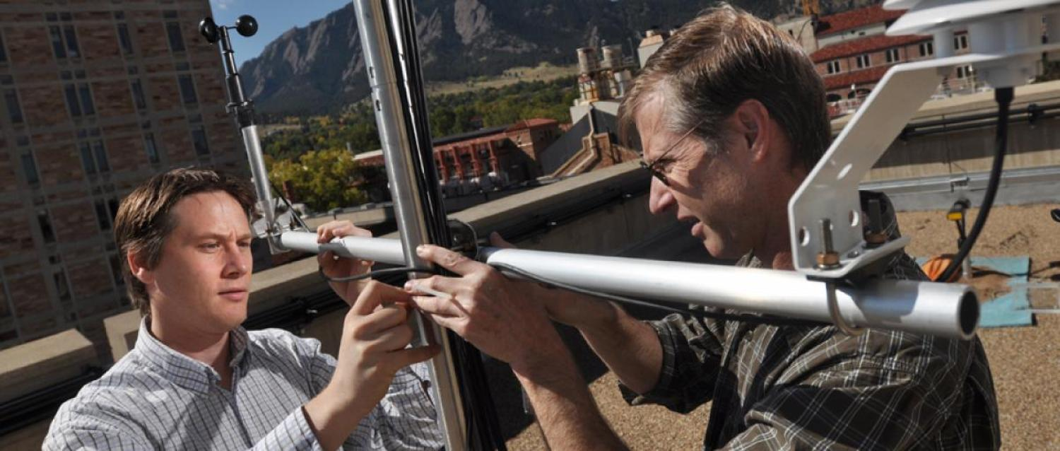Student and faculty install a piece of sustainable technology on a rooftop.