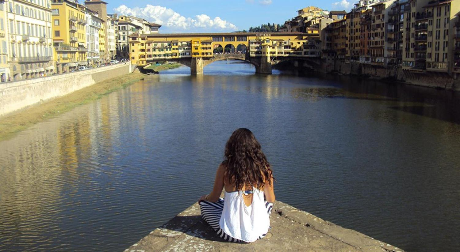 Student sitting along the Arno in Florence, Italy.