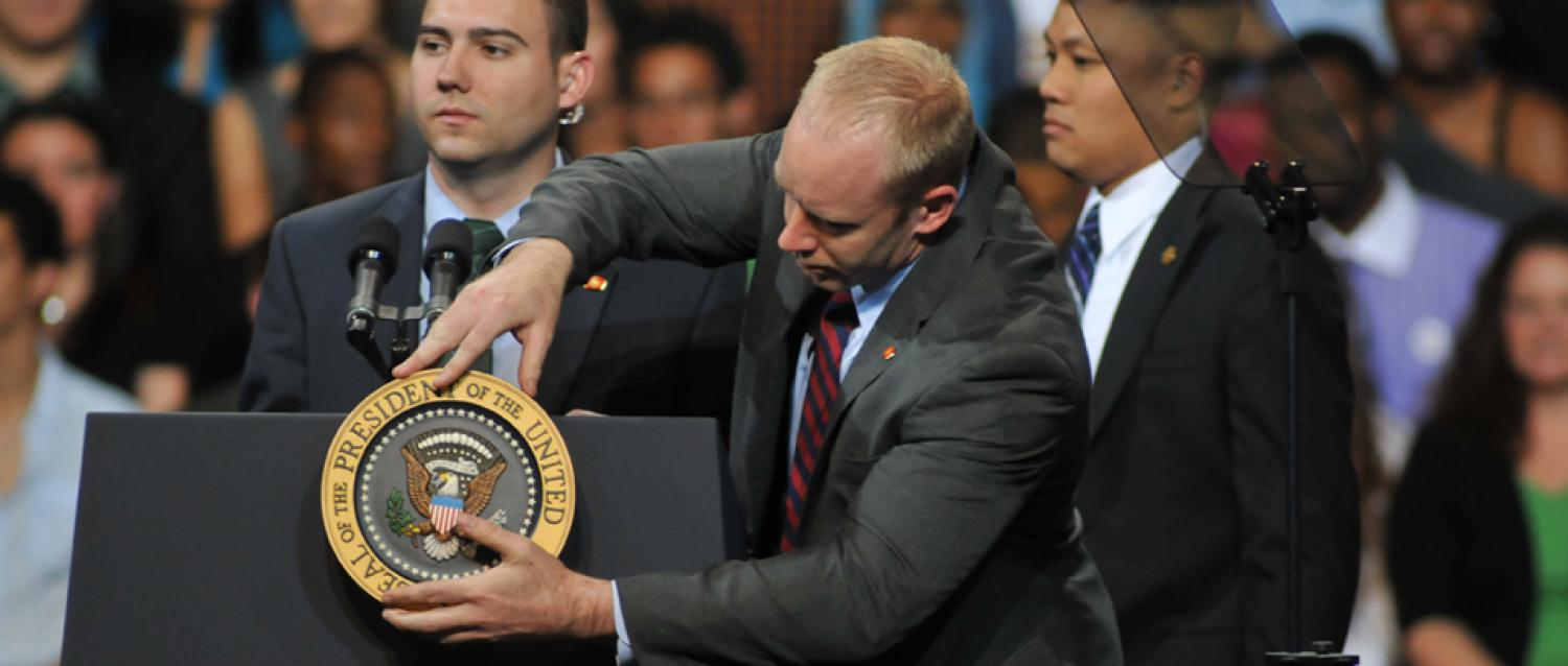 Photograph of a political aide adjusting the U.S. seal