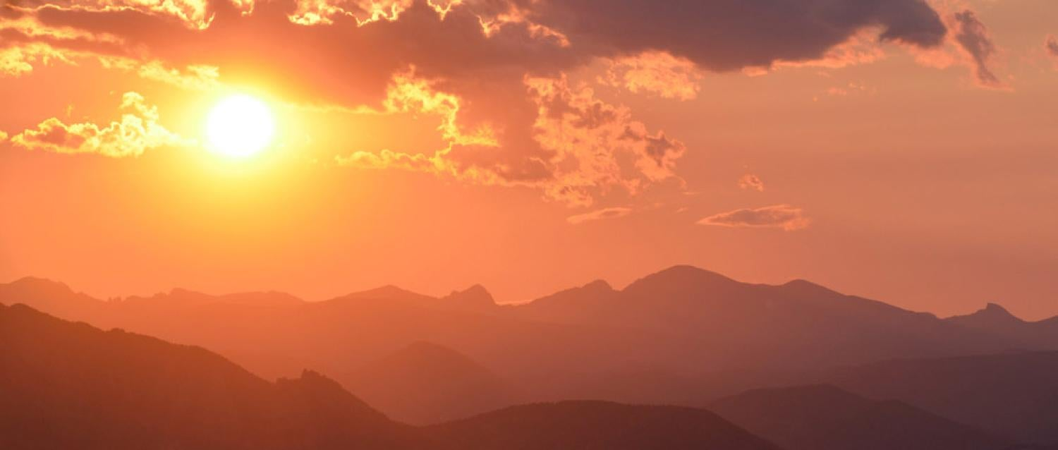 Photograph of the sunset over mountains.
