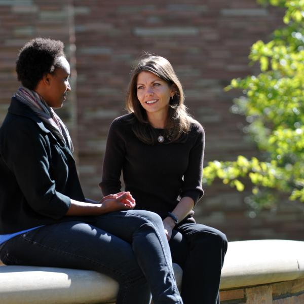 Two faculty members sitting and talking outside