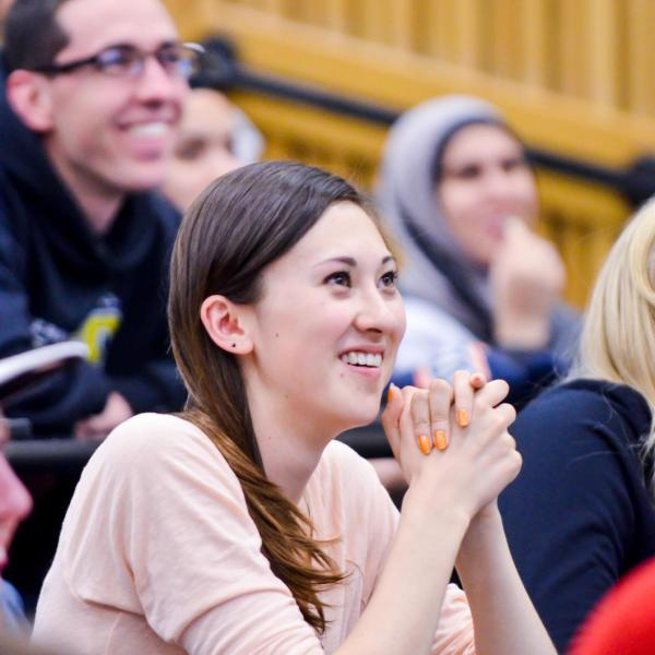 A girl sitting in a lecture class smiling