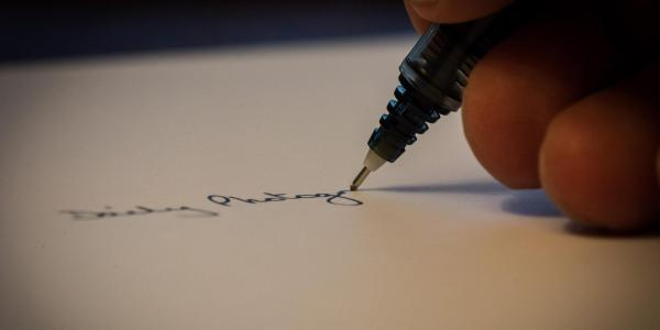 Macro photograph of a man writing on a piece of paper.