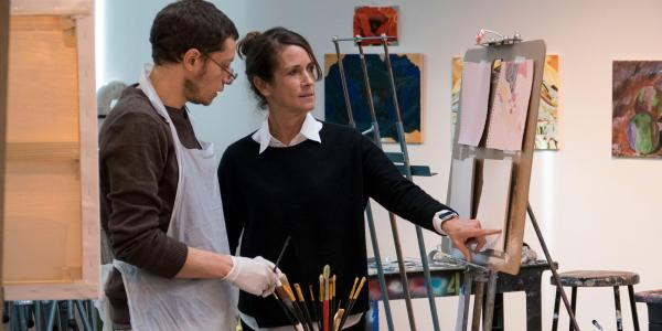 Student working with professor in front of an easel