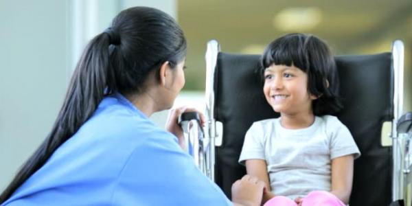 A nurse talks with a young, smiling child.
