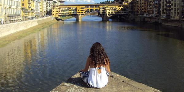 Student sitting near the Arno in Florence, Italy.