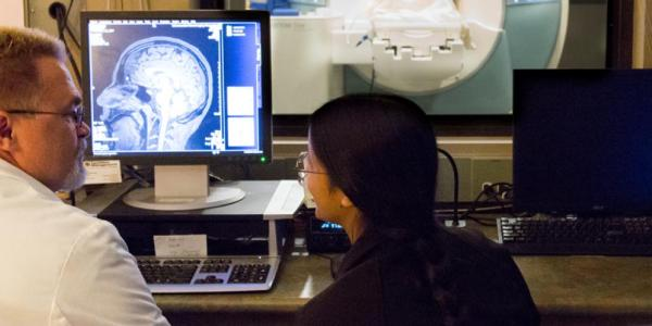 Two researchers looking at brain scans.