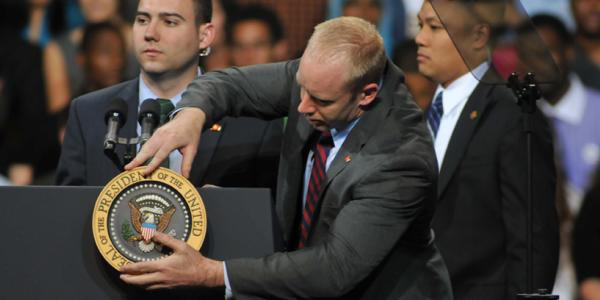 Political aide adjusts the medal on a U.S. political stage.