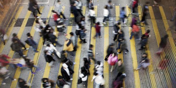 A bunch of people walking across a crosswalk.