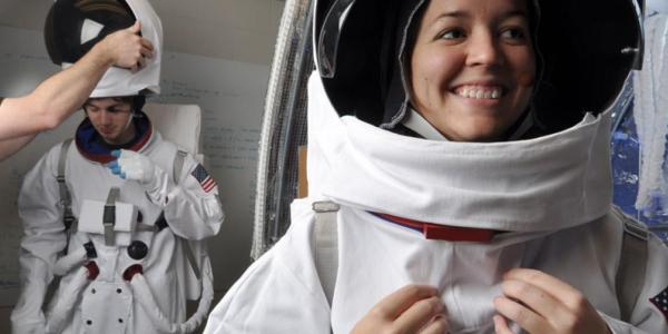 Two grinning students try on astronaut uniforms.