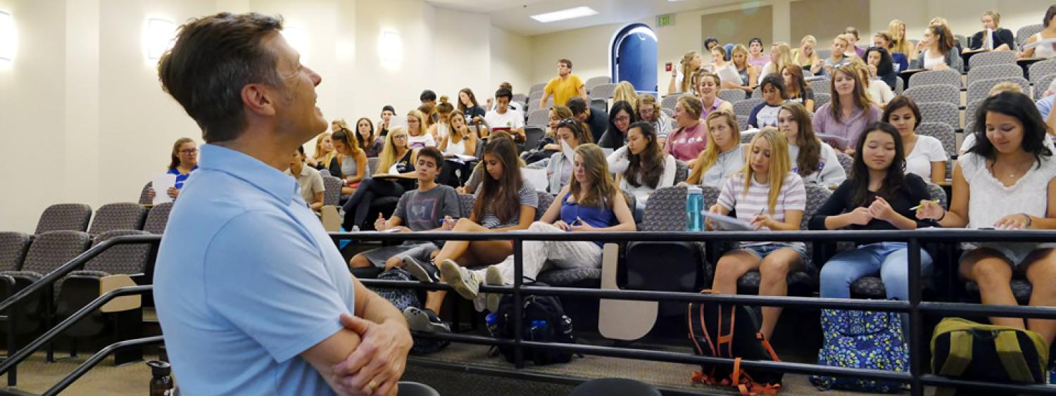 A professor addresses a classroom full of students.