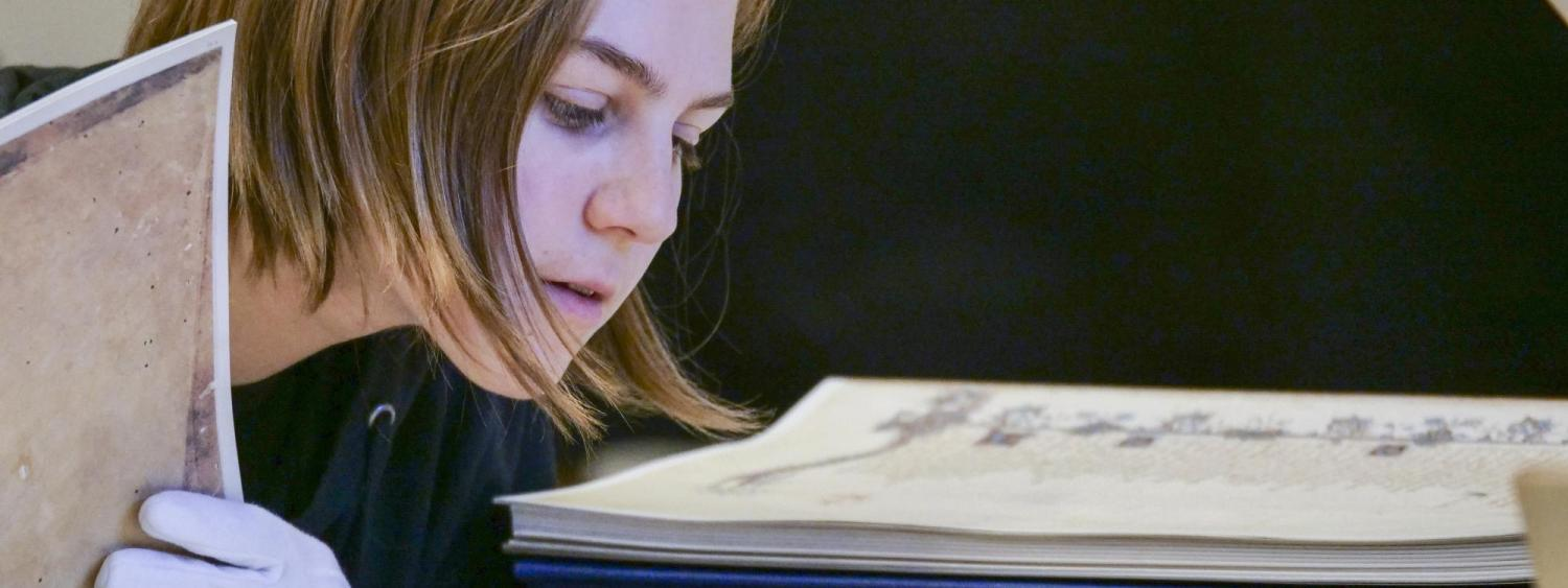 Photograph of a student looking at a historical book.