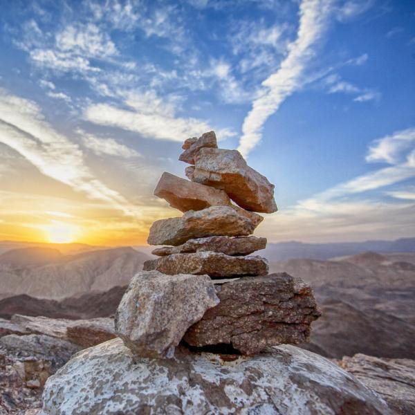 balanced rock cairn at sunset