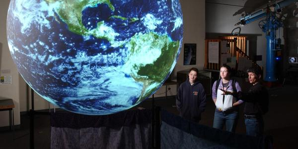 Two students and a faculty member analyze a globe.
