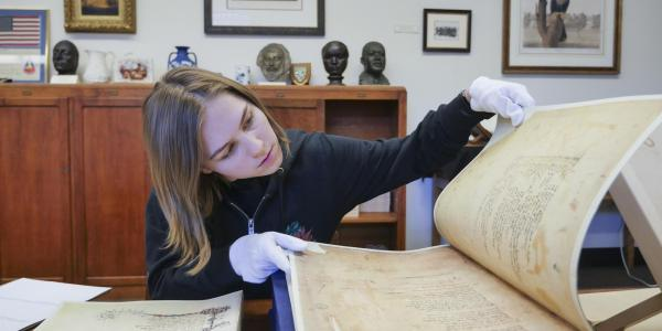 Student opens a historic text using gloves in the library archives.