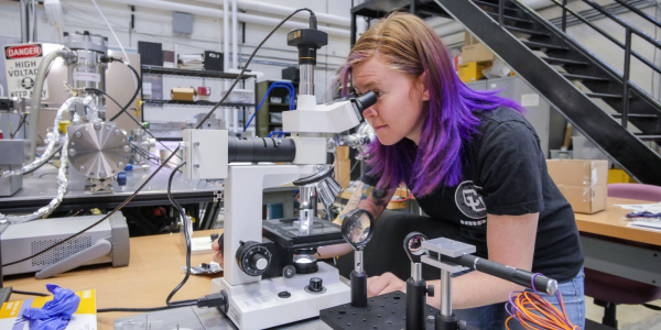 A woman analyzes a sample of material through a microscope as part of a physics experiment
