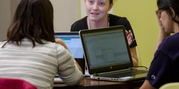 Coach assisting two students in computer lab