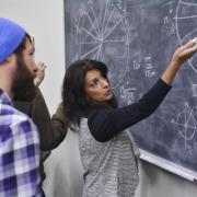 instructor at blackboard explaining algorithm